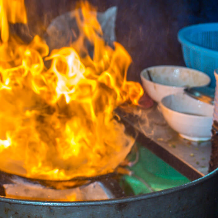 Guay Tiew Kua Gai is cooked over an open flame using pork fat