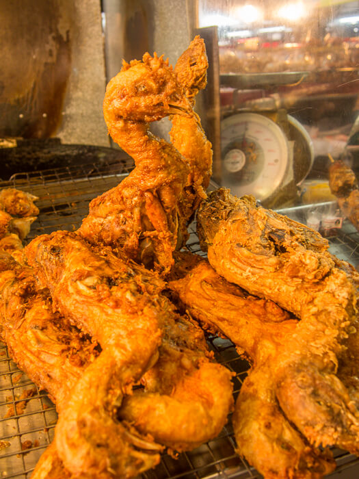 whole deep-fried chickens at a market in thailand
